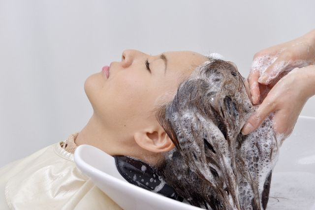 美容院でシャンプーをしてもらう女性